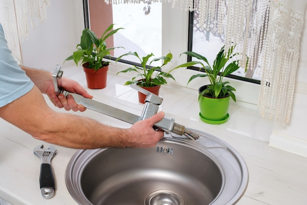 Mãos de encanador removem a velha torneira da pia da cozinha
