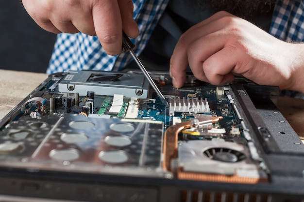 Mãos de engenheiro masculino reparam laptop com vista de closeup de chave de fenda. tecnologia de reparo de dispositivos eletrônicos