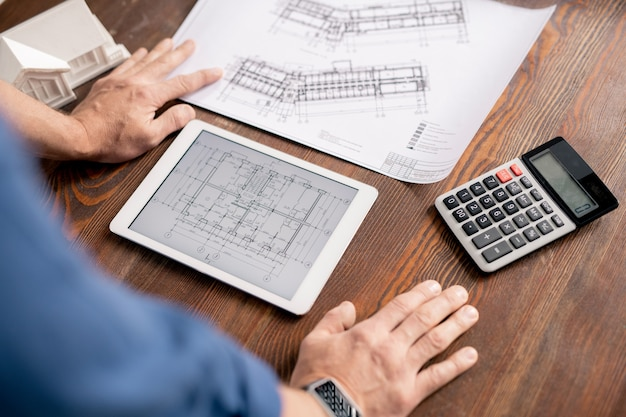 Mãos de engenheiro moderno inclinando-se sobre a mesa de madeira enquanto se inclina sobre o tablet com desenho eletrônico