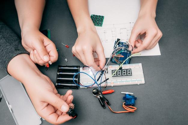 Mãos de engenheiros conectando componentes eletrônicos.
