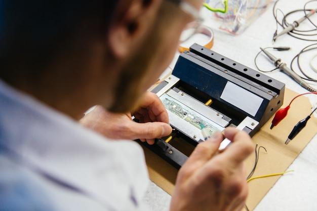 Mãos de especialista em pesquisa jovem trabalhando no laboratório eletrônico