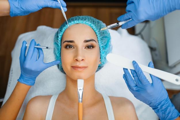 Mãos de esteticista com ferramentas de trabalho no rosto do paciente feminino. procedimento de rejuvenescimento em salão de esteticista. médico e mulher, cirurgia estética contra rugas e envelhecimento