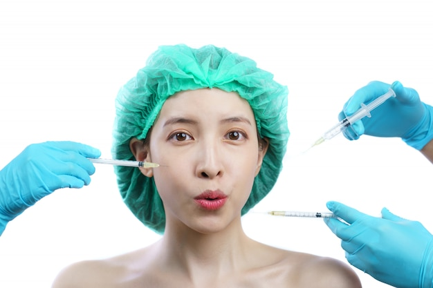 Mãos de esteticista injetando toxina botulínica tipo a no rosto de mulher asiática.