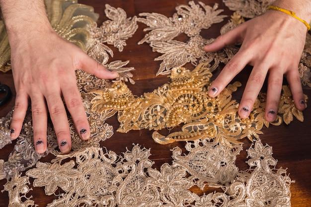 Mãos de estilista com tecido rendado de seda, decorando com bordado.