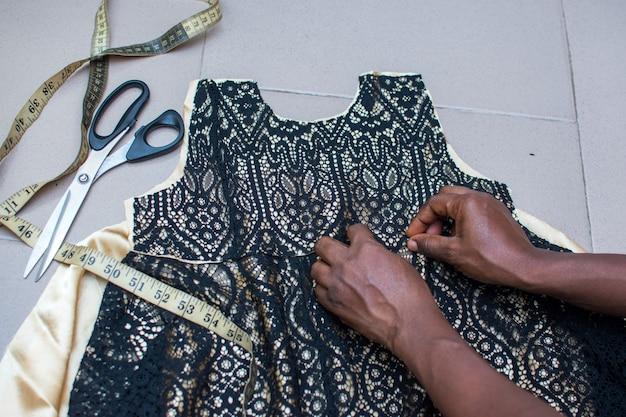 Mãos de estilistas africanos trabalhando em um vestido com uma fita métrica e uma tesoura nas proximidades
