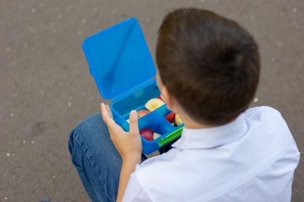 Mãos de estudante de camisa branca com gravata azul, segurando a lancheira azul com maçãs.