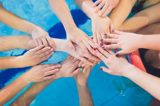Mãos de família de quatro pessoas com pulseiras com tudo incluído. equipe familiar por piscina, férias de verão.