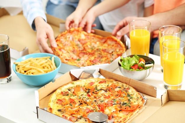 Mãos de família feliz comendo pizza.