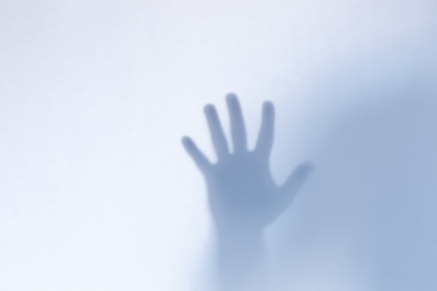 Mãos de fantasma assustador desfocado por trás de um copo branco