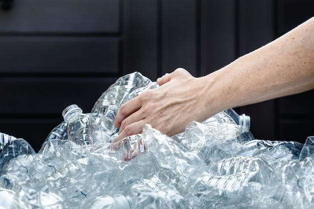 Mãos de femals agarrando garrafas de plástico para coletar e jogá-las no lixo