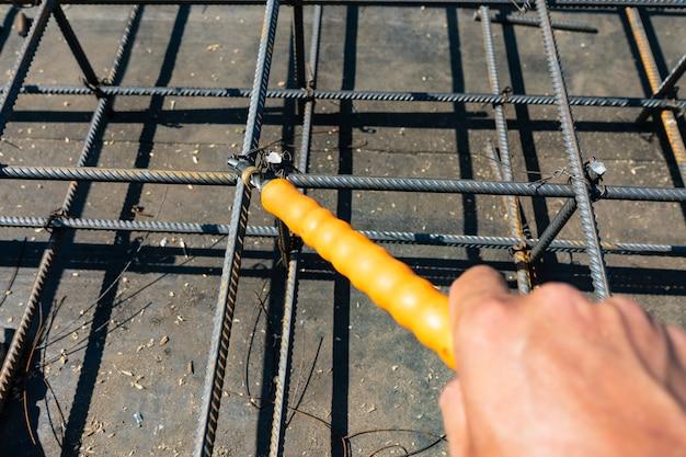 Mãos de fios de trabalhador de construtor para tricotar hastes de metal.