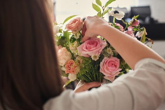 Mãos de florista coletar buquê de casamento. florista no trabalho