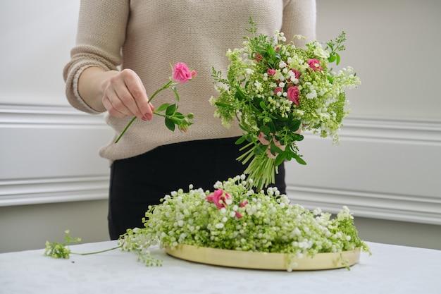 Mãos de florista mulher fazendo buquê