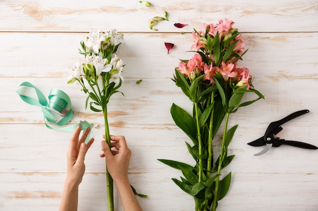 Mãos de florista vista superior fazendo buquê de flores