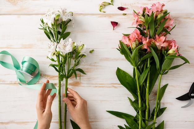 Mãos de florista vista superior fazendo buquê