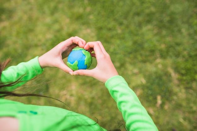 Mãos de forma de coração envolve o planeta de plasticina colorida