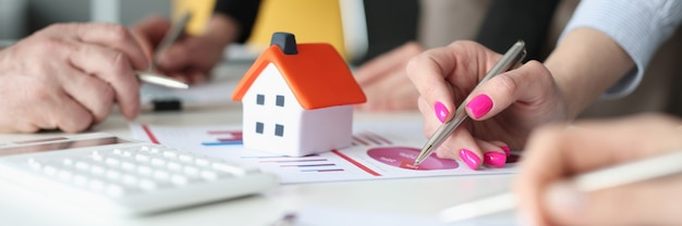 Mãos de funcionários com canetas e gráficos de negócios e pequena casa na mesa. conceito de consultoria e análise imobiliária
