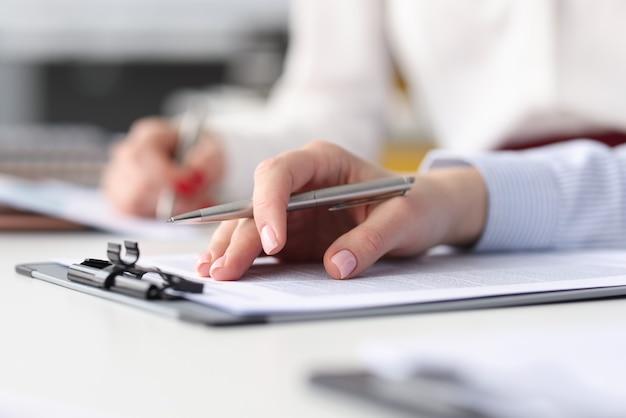 Mãos de funcionários com documentos e canetas na mesa de trabalho