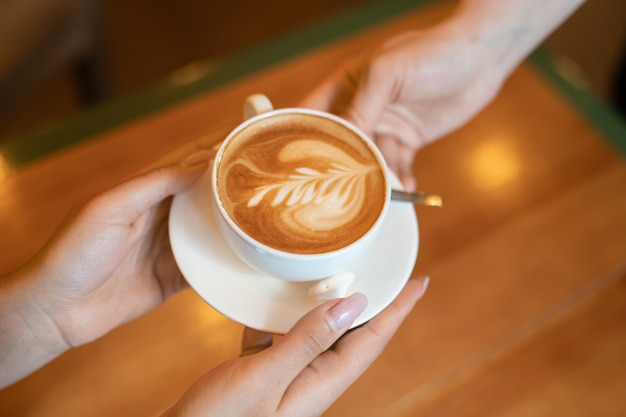 Mãos de garçonete passando uma xícara de cappuccino fresco para uma cliente em uma mesa de madeira em um café ou restaurante contemporâneo