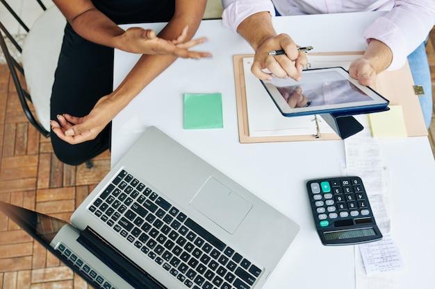 Mãos de gerentes financeiros discutindo relatórios e diagramas no computador tablet na reunião, vista de cima