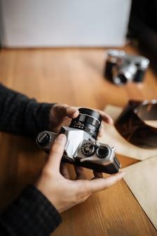 Mãos de homem ajusta a câmera retrô de lente em uma mesa de madeira