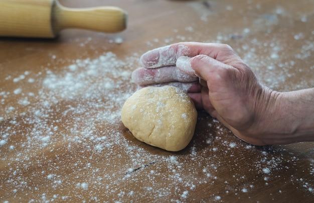 Mãos de homem amassando pão em uma mesa de madeira com farinha polvilhada