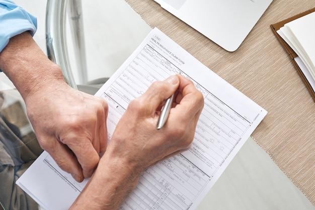 Mãos de homem aposentado sênior contemporâneo com caneta preenchendo formulário de seguro de saúde enquanto está sentado à mesa