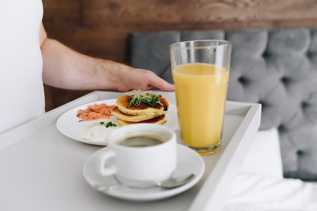 Mãos de homem caucasiano, trazendo saboroso café da manhã na cama na bandeja