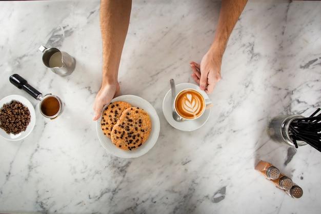 Mãos de homem com biscoitos e um cappuccino
