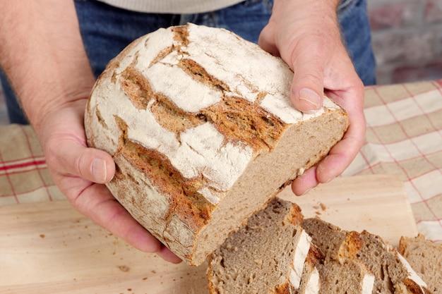 Mãos de homem com pão fresco na mesa de madeira
