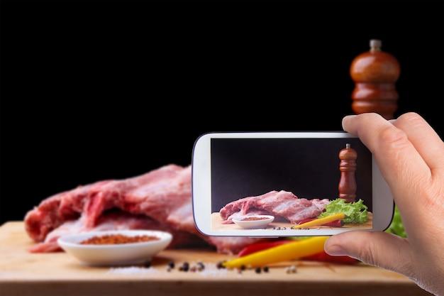 Mãos de homem com smartphone tirando foto costelas cruas sobre uma tábua rústica com sal, pimenta e moedor de especiarias.