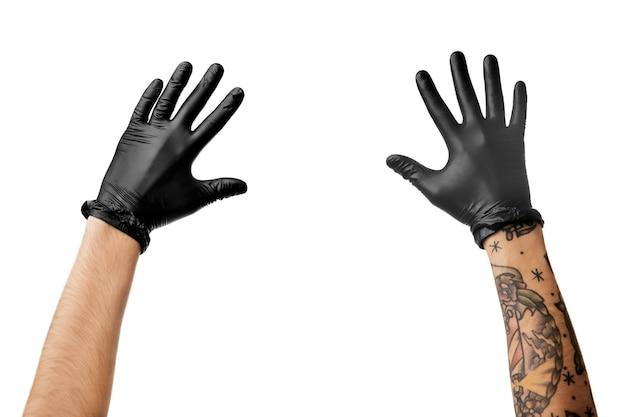 Mãos de homem com tatuagem em luvas de látex pretas
