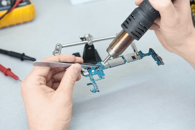 Mãos de homem consertando placa de circuito impresso de celular defeituoso desmontado em seu local de trabalho, segurando componentes eletrônicos com pinças e usando ferro de solda