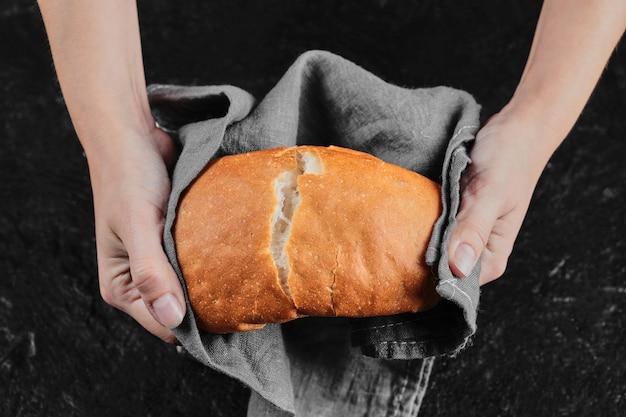 Mãos de homem cortando pão ao meio na mesa escura com toalha de mesa.