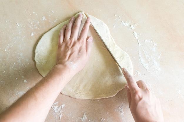Mãos de homem, corte a massa crua