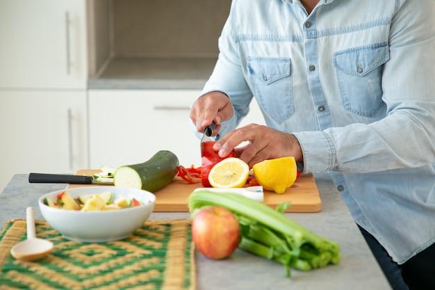 Mãos de homem cozinhando salada, corte de legumes frescos na tábua na cozinha. tiro recortado, close up. conceito de comida saudável