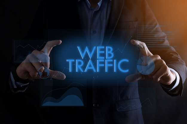 Mãos de homem de negócios segurando a inscrição web tráfego com diferentes gráficos. conceito de negócio bem-sucedido. melhoria de tráfego do site.