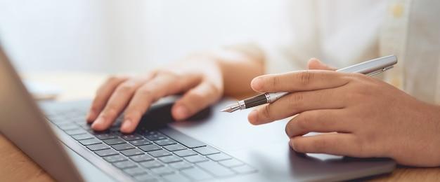 Mãos de homem de negócios usando o computador portátil com caneta e segurando o curso de vários on-line.