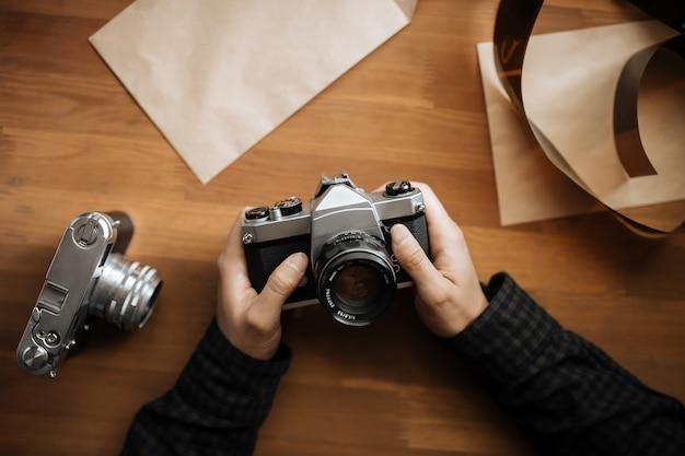 Mãos de homem detém câmera retro em uma mesa de madeira. vertical