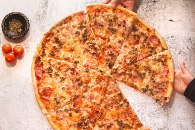 Mãos de homem e menino pegando uma fatia de pizza, close-up. pai e filho comendo
