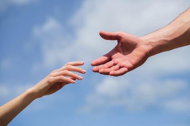 Mãos de homem e mulher alcançando um ao outro, apoio.