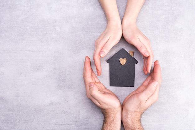 Mãos de homem e mulher cercam um modelo de uma casa escura. conceito imobiliário e seguro, vista plana, vista superior