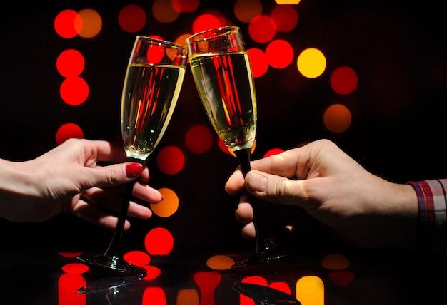 Mãos de homem e mulher com taças cheias de champanhe. felicidades.