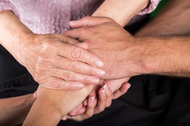 Mãos de homem e mulher segurando as mãos de uma mulher idosa