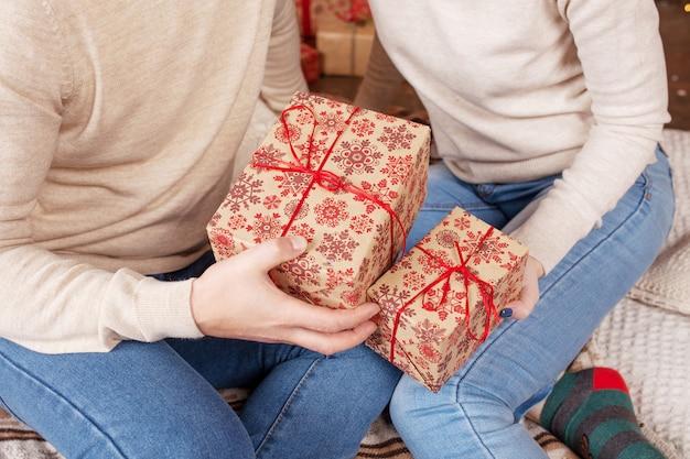 Mãos de homem e mulher segurando uma caixas de presente de natal. natal, ano novo.