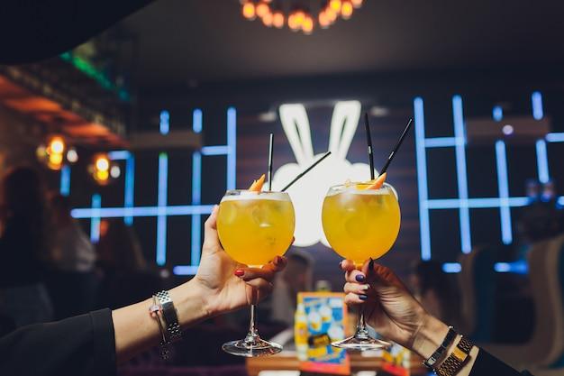 Mãos de homem e mulher torcendo com copos de champanhe rosa.