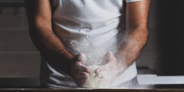 Mãos de homem, farinha e massa.