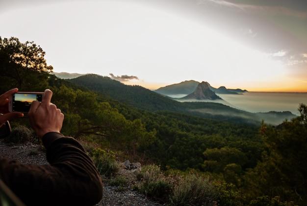 Mãos de homem fazendo fotos em seu telefone de uma bela vista da montanha e do mar no meio do nevoeiro e do pôr do sol em chipre