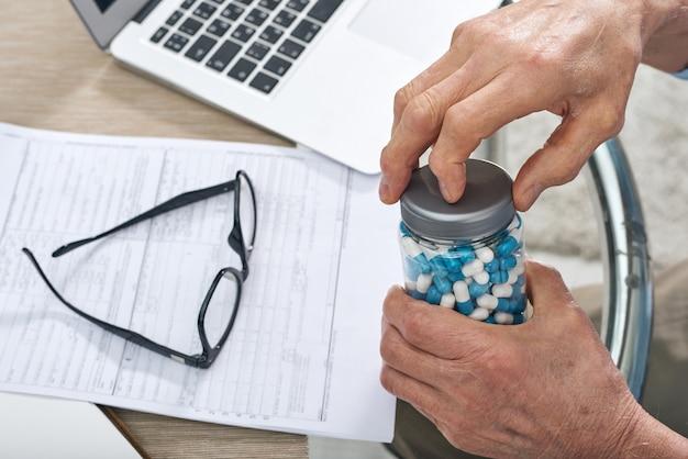 Mãos de homem idoso doente descobrindo o frasco com comprimidos para tomar remédio enquanto está sentado à mesa durante o trabalho com documentos