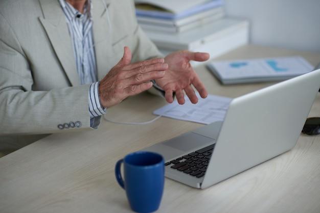 Mãos de homem irreconhecível, com videochamada no laptop e aplaudindo